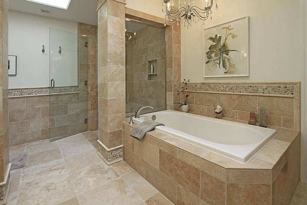 A gorgeous white framed wall art hangs above the brick lower wall in this beige master bathroom boasting a walk-in shower and drop-in bathtub lighted by a fancy chandelier.