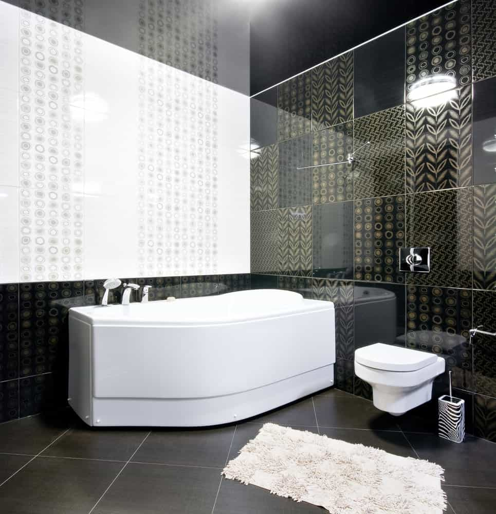 This charming bathroom has chic elements in the golden designs imbued on the black-tiled walls that are perfectly paired with a black-tiled flooring and black ceiling that emphasizes the white porcelain tub and toilet.