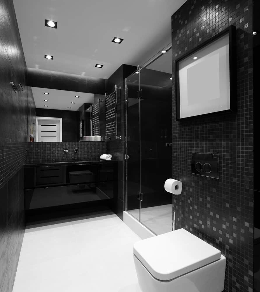 This black walls of the bathroom match with sleek black vanity with small black backsplash tiles. It also features a shower area that has a glass door and modern shower fixtures.