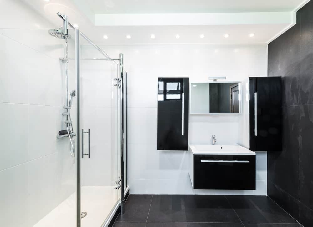 The black tiles of the bathroom flooring seamlessly extend to the wall. This is then contrasted by the adjacent white wall of the vanity area that has floating sleek black cabinets flanking the sink.