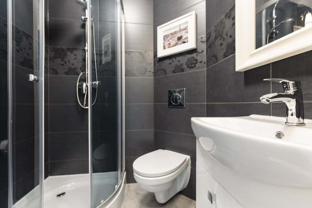 This is a simple and small bathroom with black-tiled walls that has a different set of patterned black tiles running the middle. This makes the white toilet and sink stand out.