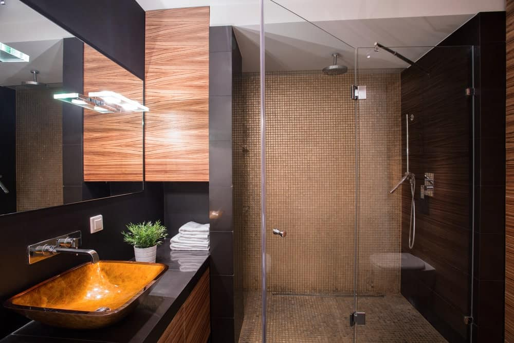 This luxurious bathroom has black walls paired with brown and wooden elements of the sink and the tiles of the shower area that has a glass door.
