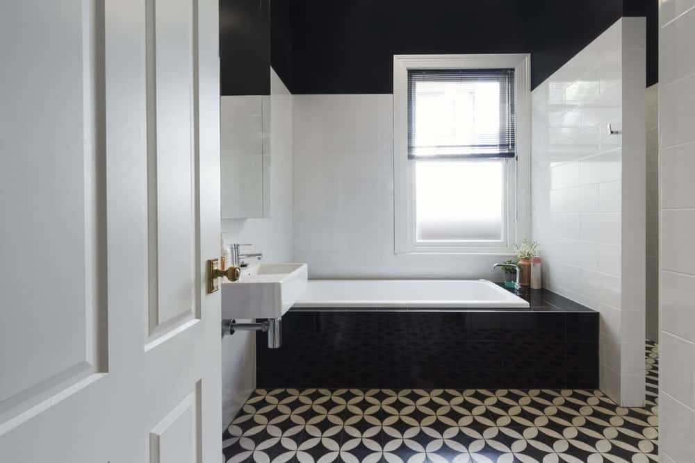 There is a brilliant white window above the bathtub that is inlaid with black tiles that match the black upper walls. This theme is complemented by black and white flooring with patterned tiles.
