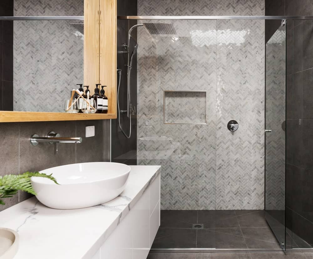 The shower area of this bathroom has a glass door and a wall made of herringbone gray tiles that complement the black tiles of the floor and walls as well as the white vanity with white marble countertop.