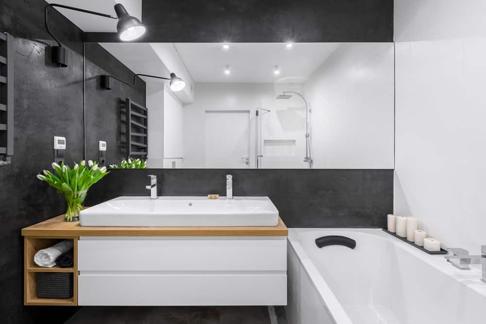 The black-tiled walls of this bathroom are contrasted by the white bathtub and sink that has a wide vanity mirror extending all the way to the head of the bathtub.