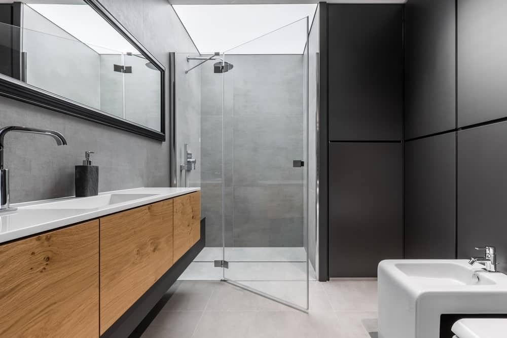 This bathroom has matte black wall panels that match the black wooden frame of the wide vanity mirror against the gray stone backsplash.