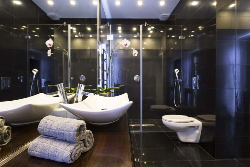 This elegant bathroom is dominated by the shiny black tiles of the flooring and walls that reflect the warm yellow lights of the pin lights mounted on the white ceiling.