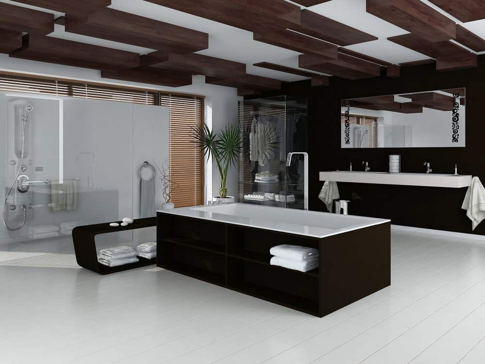 This spacious and luxurious bathroom has white flooring that emphasizes the black walls and black wooden housing of the bathtub that has built-in shelves. This is complemented by the irregular wooden beams of the ceiling.