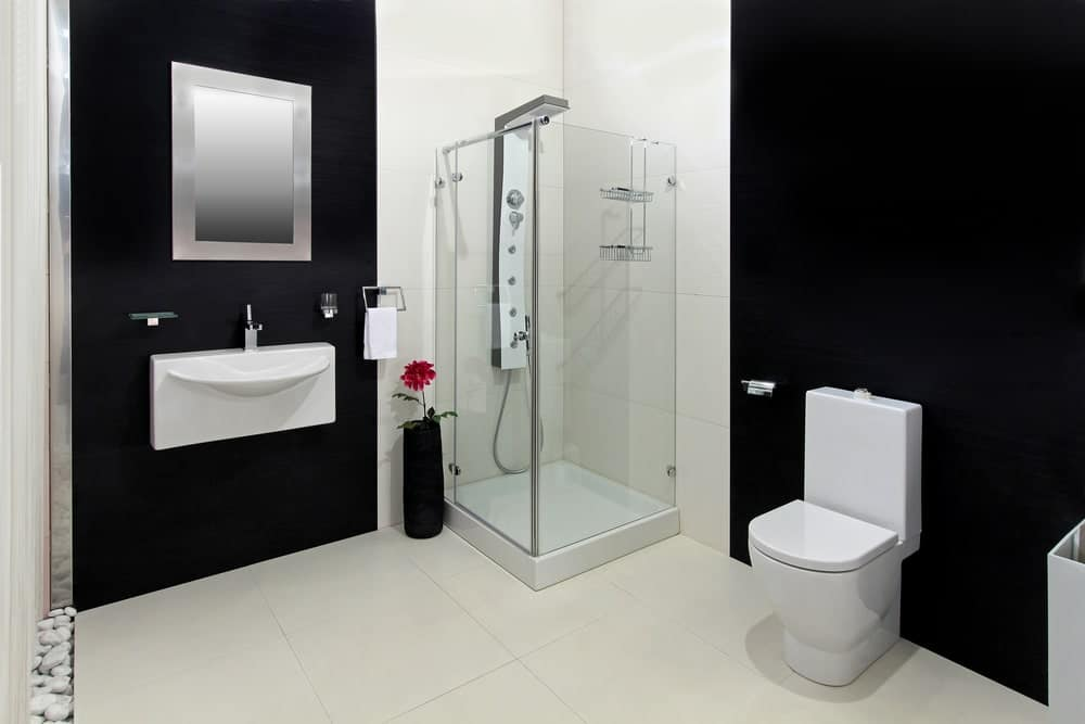 The white-tiled flooring is edged with decorative river stones that contrast the pitch-black walls that emphasize the smooth white porcelain toilet and floating sink.