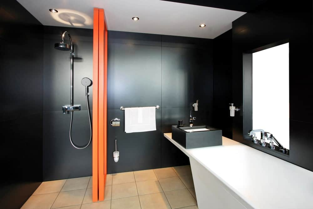 This black walls of the bathroom feature a wooden orange divider that separates the shower area with modern fixtures and the vanity area with a white countertop extending to the bathtub.
