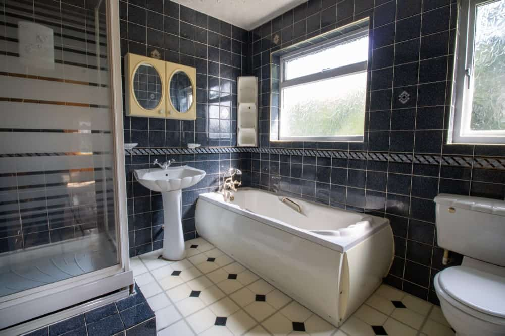 The grainy black tiles of the walls are a perfect match for the seashell designs of the porcelain sink, bathtub, and toilet for a sea-like theme.