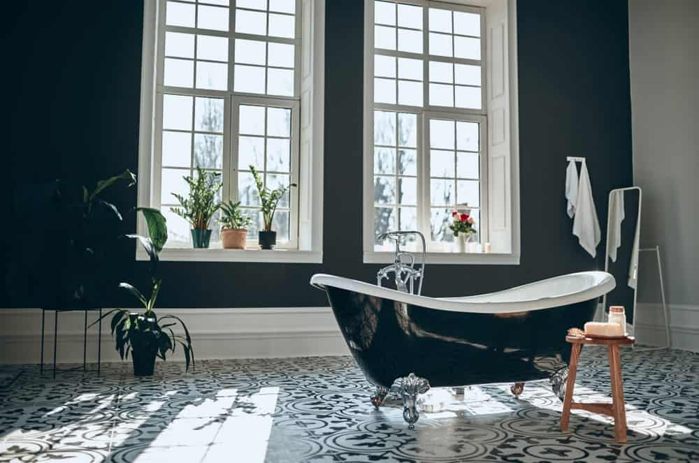 This is an airy and relaxing bathroom with a high ceiling and tall windows that brighten up the black walls, black freestanding bathtub and the patterned floor tiles.