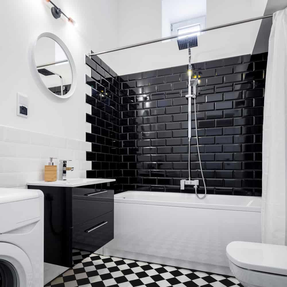 The brilliant black tiles of the shower area are arranged in a brick wall pattern that contrasts the white bathtub. On the other hand, the black floating vanity is contrasted by the white wall behind it.