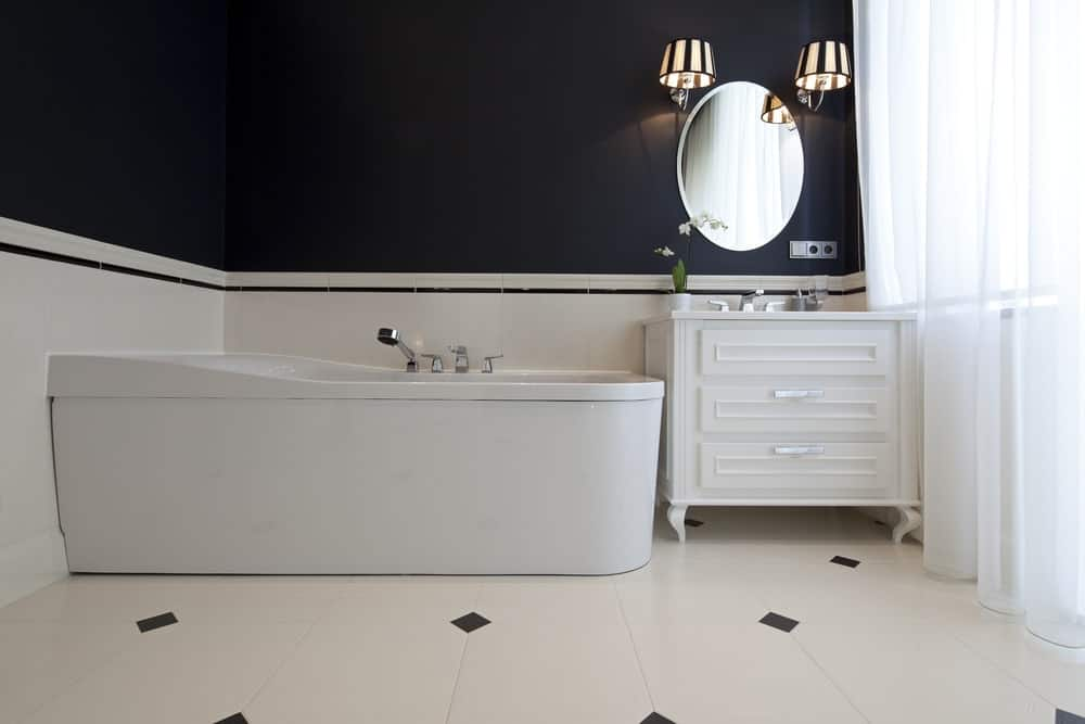 The bathtub is in a corner beside the white wooden vanity that has an elliptical borderless vanity mirror mounted on the black upper walls.