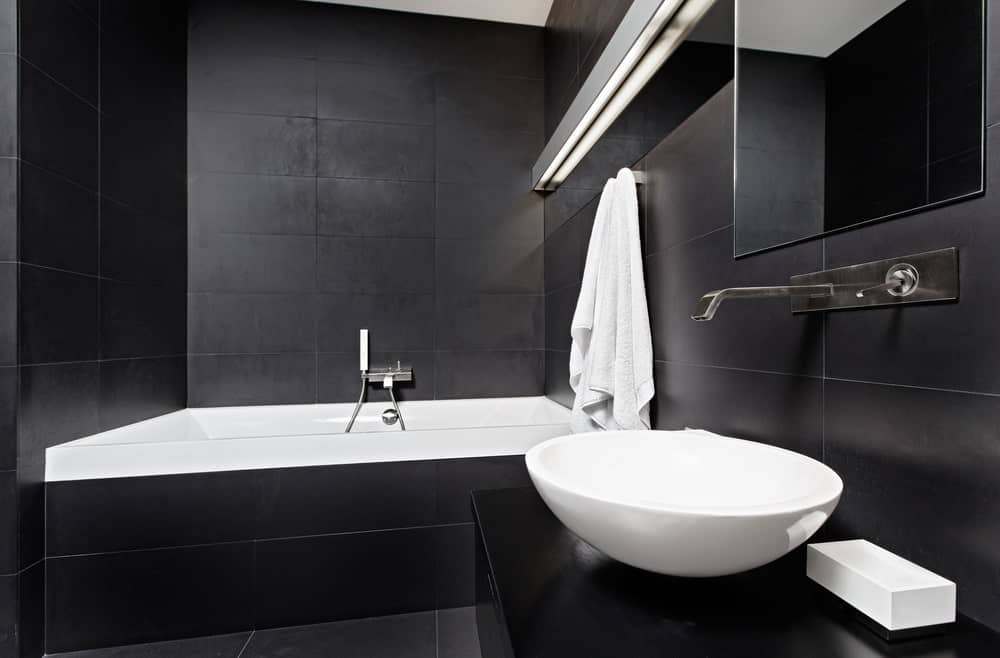 The uniform black tiles of the flooring, walls and the bathtub housing make the white porcelain sink and tub stand out illuminated by a wall-mounted elongated lamp.