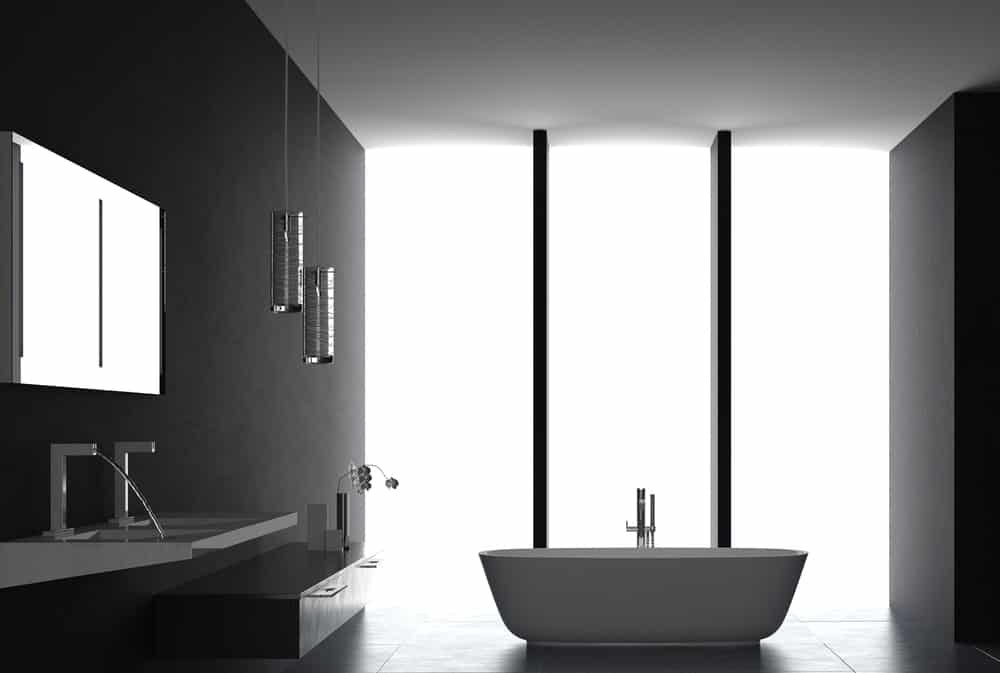 This is a black master bathroom that counteracts the dark elements with massive floor-to-ceiling windows made of frosted glass. This gives the freestanding bathtub and white modern sink a slight glow.