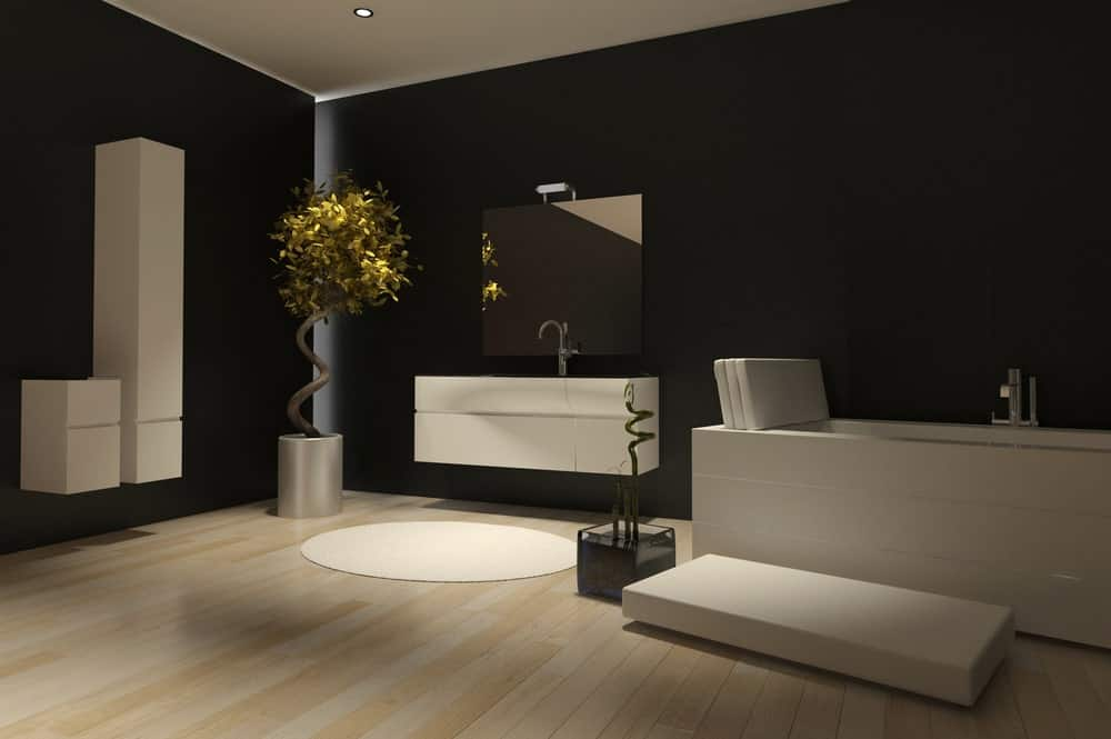 The uniform black walls are given a modern twist with backlights emphasizing the corners and floating white cabinets that match the floating vanity area beside the white bathtub.