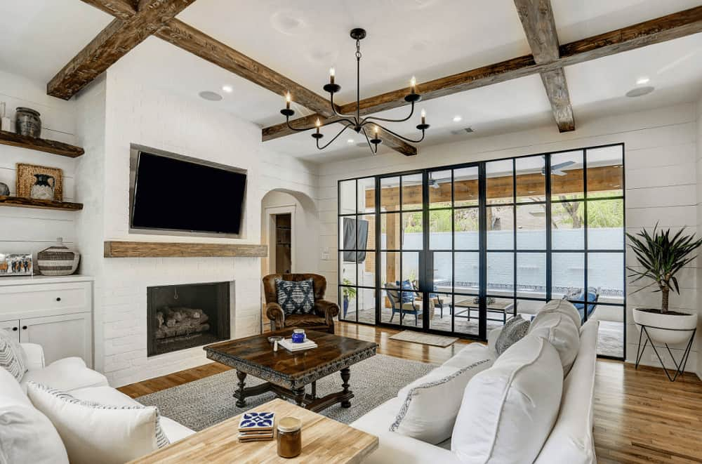 A brown leather armchair complements the dark wood coffee table accompanied by a white sectional sofa and fireplace. It is illuminated by a wrought iron chandelier that hung from the regular white ceiling framed with rustic beams.