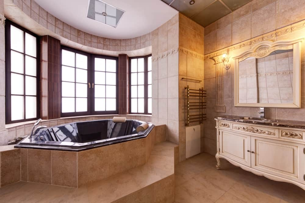 Marvelous bathroom with a carved wood vanity paired with a mirrored medicine cabinet that's lighted by wall sconces and a black soaking tub by the wooden framed windows allowing ample of natural light in.