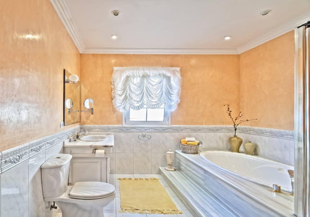 Gorgeous bathroom showcases a stylish toilet and drop-in bathtub blending in with the lower marble tile walls and flooring. The peach upper walls add a nice accent to the room.