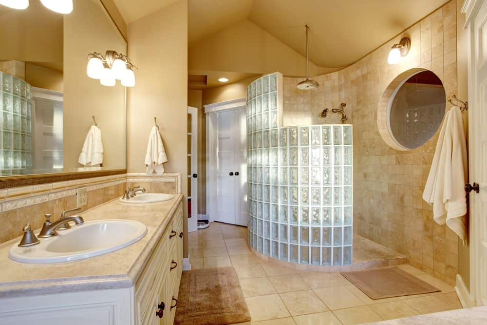 Well-lit bathroom with dual sink vanity and shower area enclosed in glass block wall. It has a cathedral ceiling and tiled flooring topped by brown rugs.