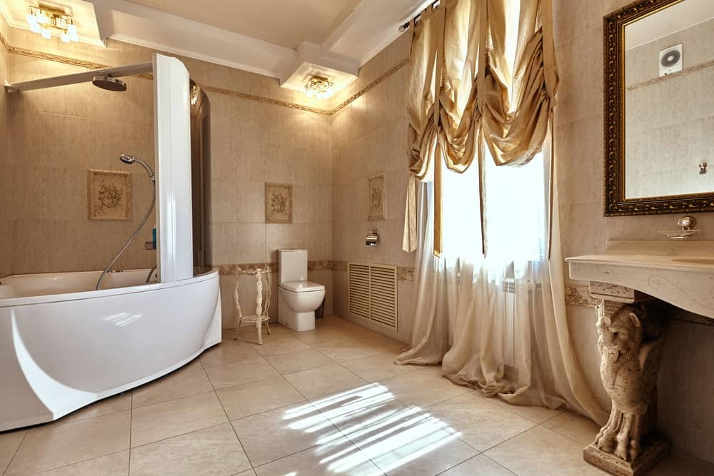 This bathroom boasts a corner tub and shower combo that sits next to the toilet paired with a white side table. It has tiled flooring and glazed windows dressed in sheer curtains.