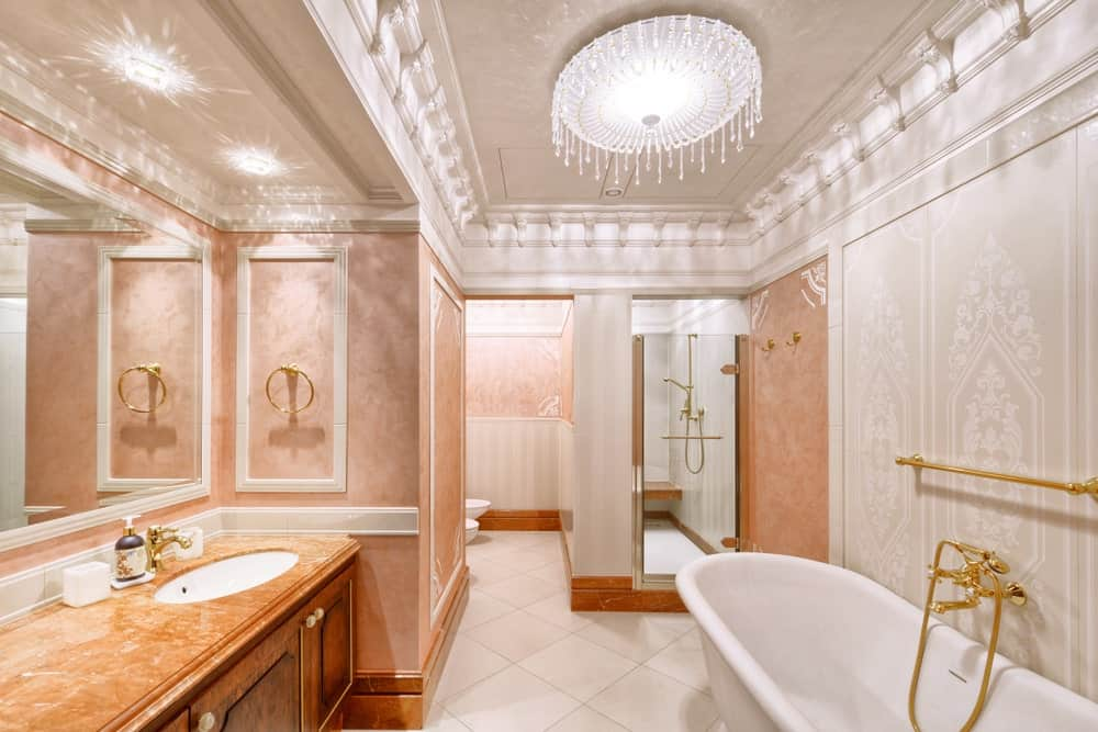 Classy bathroom illuminated by a fancy round flush light mounted on the stylish tray ceiling. It has a walk-in shower and freestanding tub with gold fixtures adding elegance to the room.