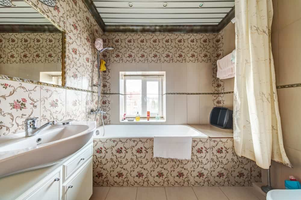 A gold framed mirror hangs over the vessel sink vanity in this country style bathroom with a shower and tub combo clad in lovely floral tiles.
