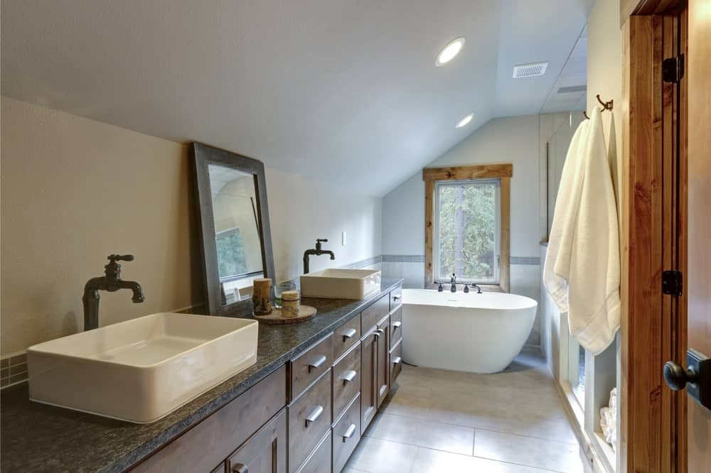 Classic bathroom offers a pedestal bathtub and lengthy vanity topped with black granite counter and vessel sinks. It has brick tile flooring and glazed window framed in natural wood.