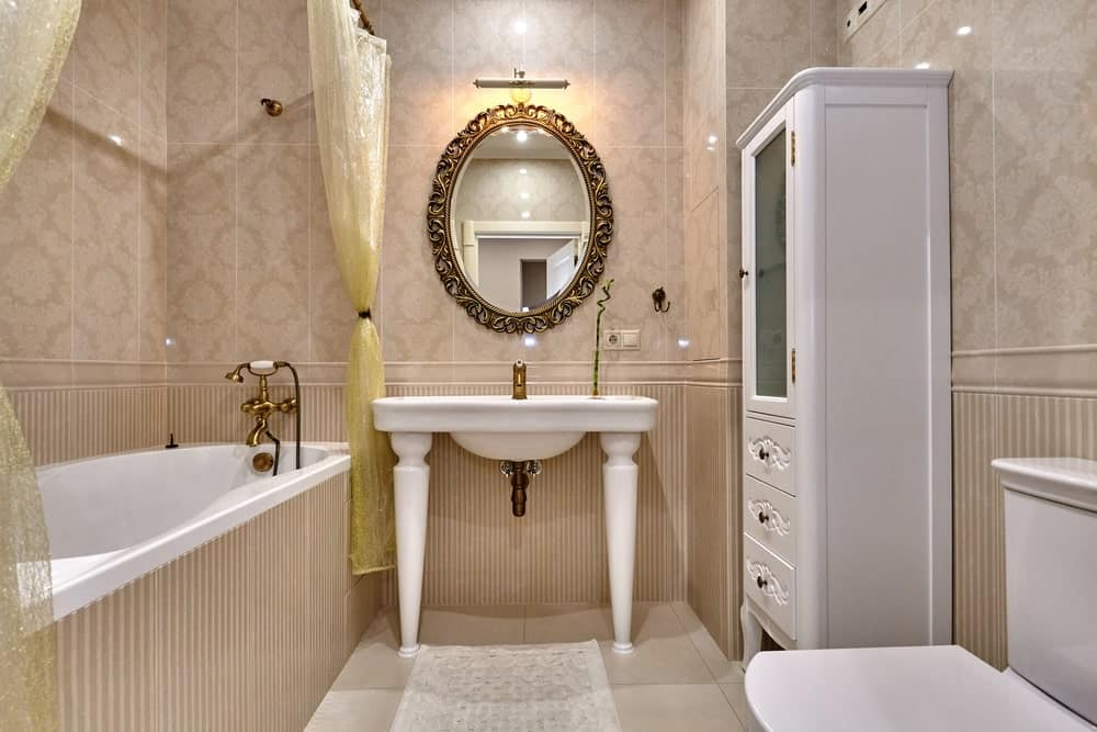 Elegant bathroom features an ornate mirror that hung over the washstand situated in between a white storage cabinet and deep soaking tub clad in beadboard tiles.
