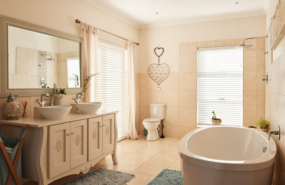 Charming bathroom offers a toilet and pedestal tub across the carved wood vanity with dual vessel sink and chrome fixtures. It has louvered windows and tiled flooring topped by shaggy rugs.