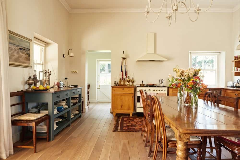 This is a cozy and homey dining area inside the cheerful beige walls and ceiling of the kitchen. This is complemented by the hardwood flooring that matches with the wooden dining table paired with wooden chairs of the same hue.