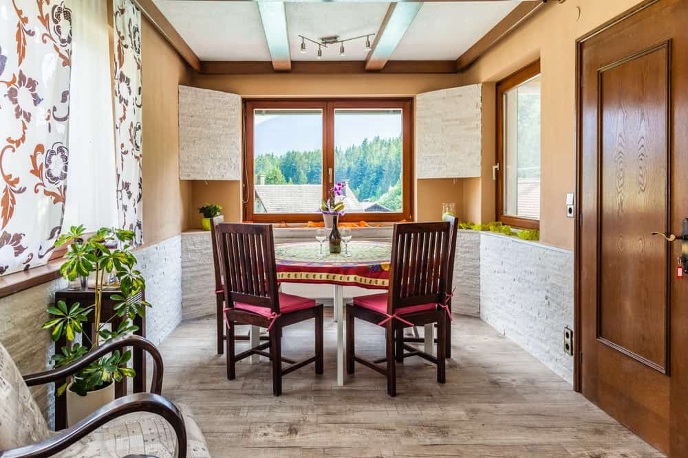 This small dining room is surrounded by orange walls with windows to give a sense of space. The walls have a textured white stone wainscoting that provides a nice contrast to the dark wooden slat back dining chairs of the white round table with a colorful table cloth.