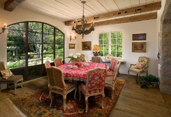 This chic dining room has a round table dominated by the pink patterned table cloth that matches with the upholstery of the surrounding wooden chairs. This also matches with the colorful patterned area rug underneath.