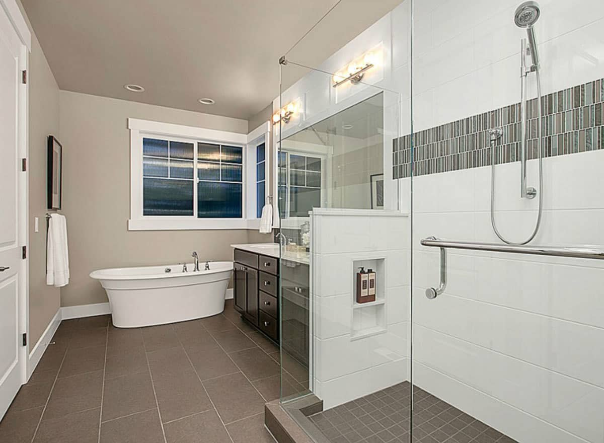 The primary bathroom has a freestanding bathtub beneath the window as well as walk-in shower area with glass walls beside the vanity that has dark wood cabinets.