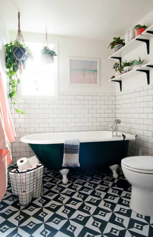 Fresh bathroom with a toilet and black clawfoot tub placed against the white brick walls. It includes a metal bin on a striking tiled floor and floating shelves filled with leafy potted plants.