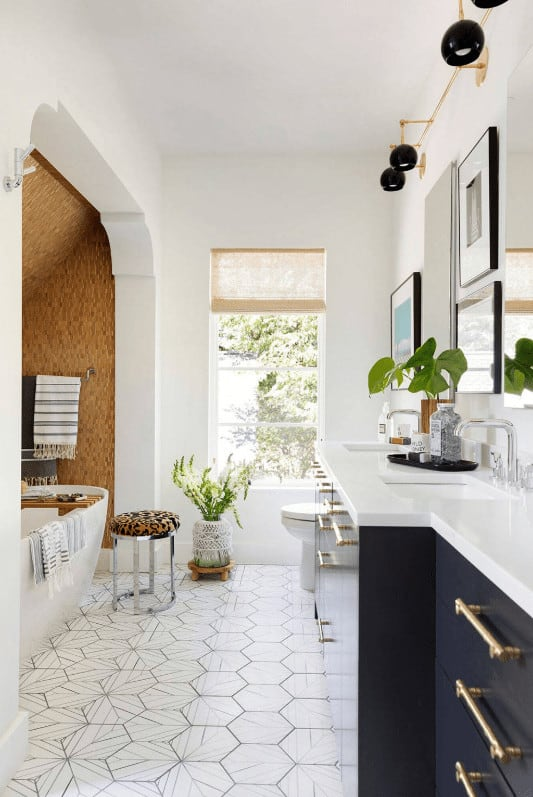 This bathroom is designed with gallery frames and black sconces matching with the dual sink vanity on a gorgeous hex tile flooring. It has a toilet and alcove bathtub paired with a metal side table.