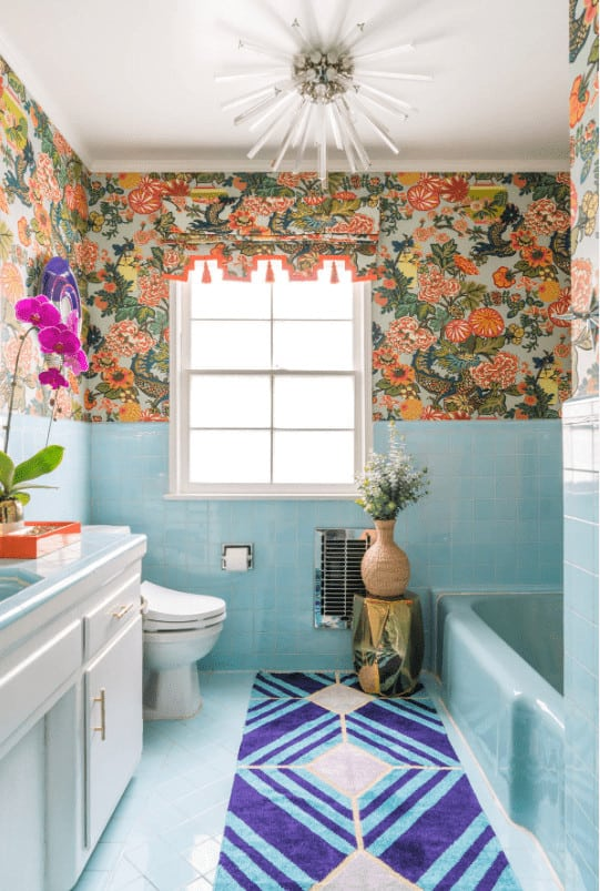 Charming bathroom with a sputnik chandelier and diamond patterned runner that lays on blue tiled flooring. It includes a lovely floral wallpaper which brings a cheerful tone in the room.