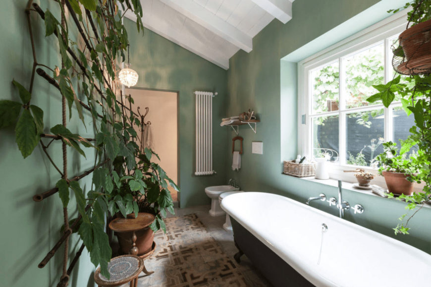 Airy bathroom with a tropical vibe from the fresh potted plants blending in with the green walls. It has a pair of toilets and a black clawfoot tub with chrome fixtures.