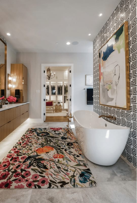 A colorful floral rug and striking patterned wall mounted with an abstract canvas add a gorgeous accent to this bathroom showcasing a freestanding tub and a double door that opens to the walk-in closet.