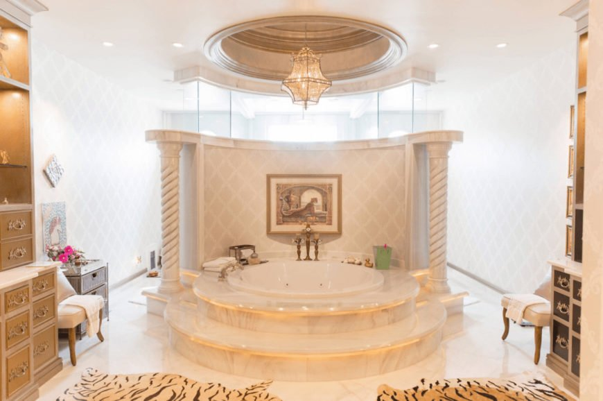 Bright bathroom features a classy drop-in bathtub lined with spiral columns. It is illuminated by a fancy pendant light that hung from the round tray ceiling.
