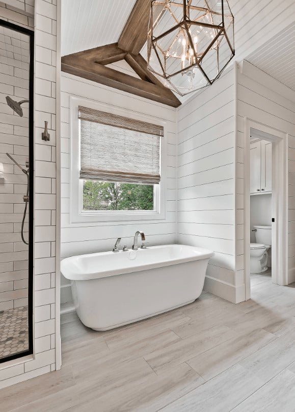 Airy bathroom illuminated by an oversized geometric pendant that hung from the shiplap ceiling lined with wood beams. It sits in between the toilet area and walk-in shower with chrome fixtures.