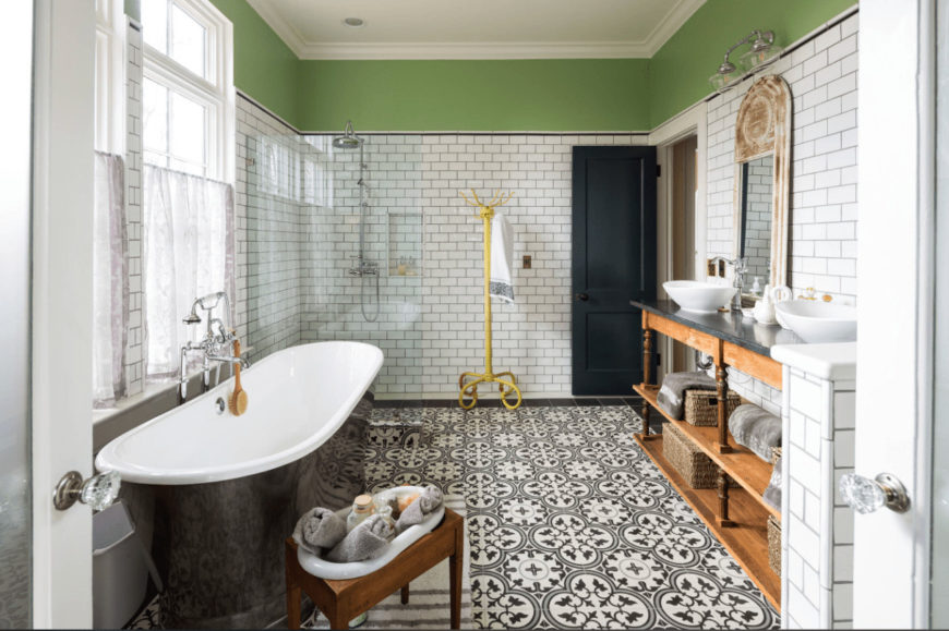 Green upper wall and decorative tiled flooring add a gorgeous accent to this farmhouse bathroom with a walk-in shower and black bathtub that sits across the wooden washstand with dual vessel sink and distressed wood mirror.
