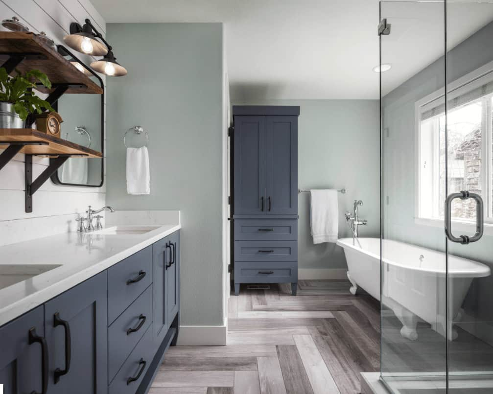 Classic bathroom with a clawfoot tub and grayish blue storage cabinet that matches with the vanity fitted with dual sink and chrome fixtures. It is placed beneath wooden shelves and black framed mirror lighted by sconces.