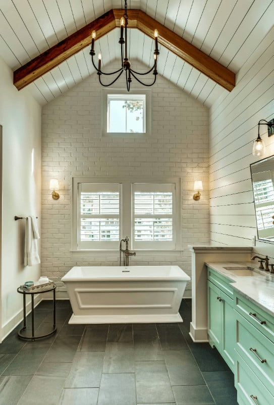 Cozy bathroom showcases a white brick accent wall and shiplap ceiling lined with wood beam. It is illuminated by wall sconces and a wrought iron chandelier that hung over the black tiled flooring.