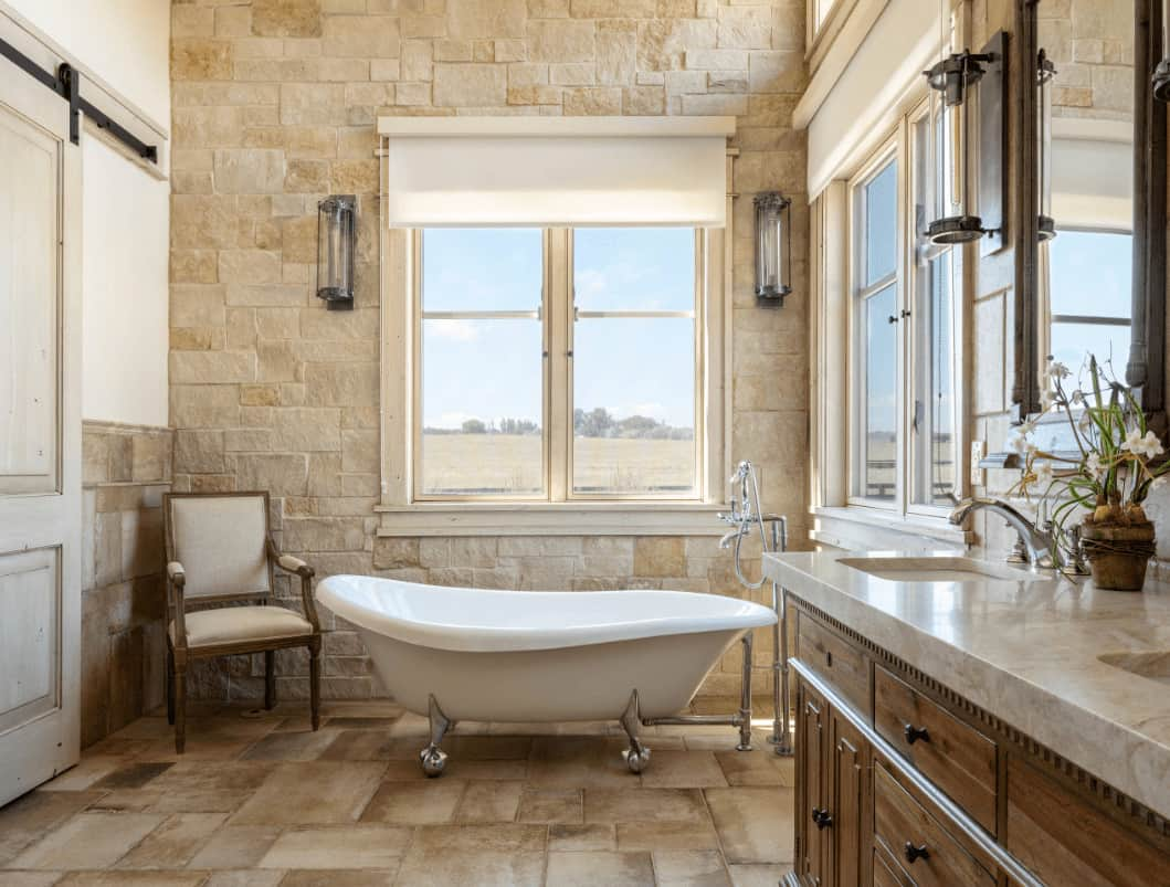 A beige cushioned armchair sits beside the clawfoot tub in this farmhouse bathroom with wooden vanity and white framed windows covered in roman shades.