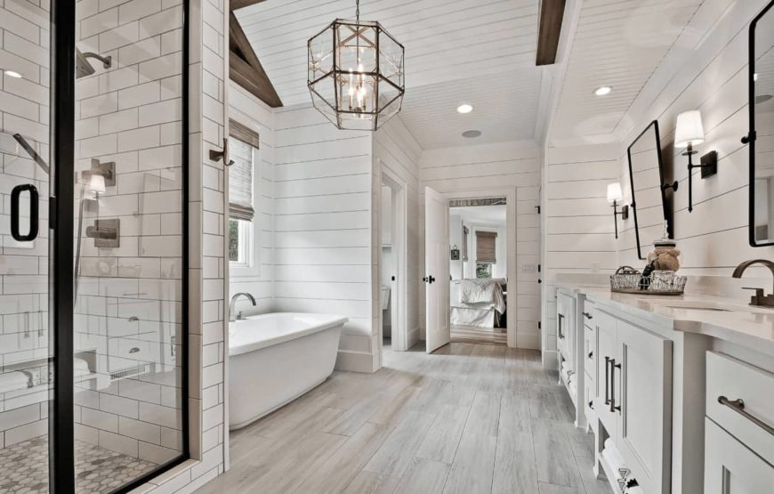 Farmhouse bathroom boasts an immense vanity and geometric chandelier that hung from the shiplap ceiling. It has a walk-in shower and a freestanding tub with gooseneck faucet sitting on the light wood plank flooring.