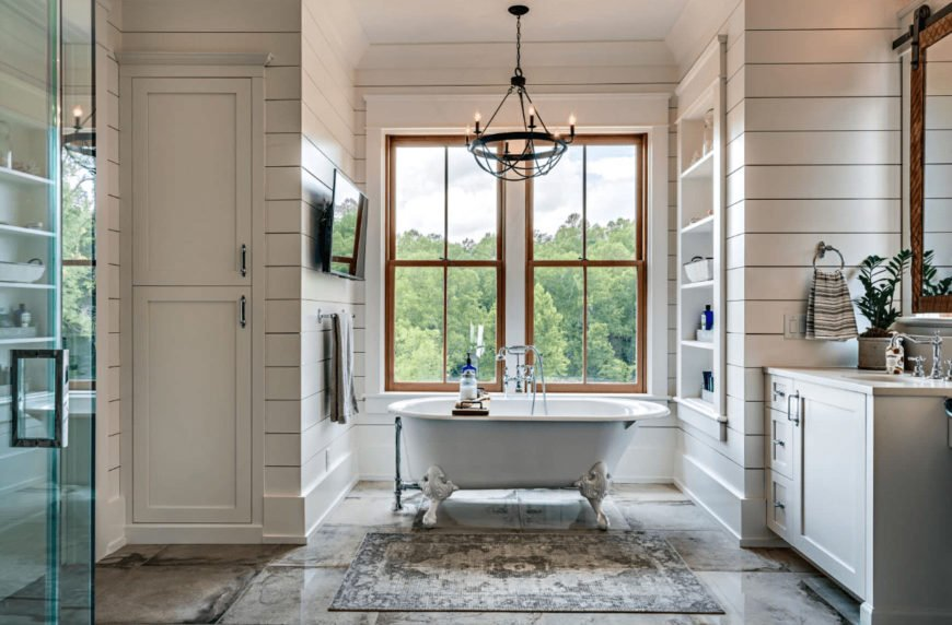 A wrought iron chandelier illuminates this farmhouse bathroom boasting a white vanity and a clawfoot tub by the wooden framed window. It has shiplap walls mounted with a flat panel TV and inset shelf.