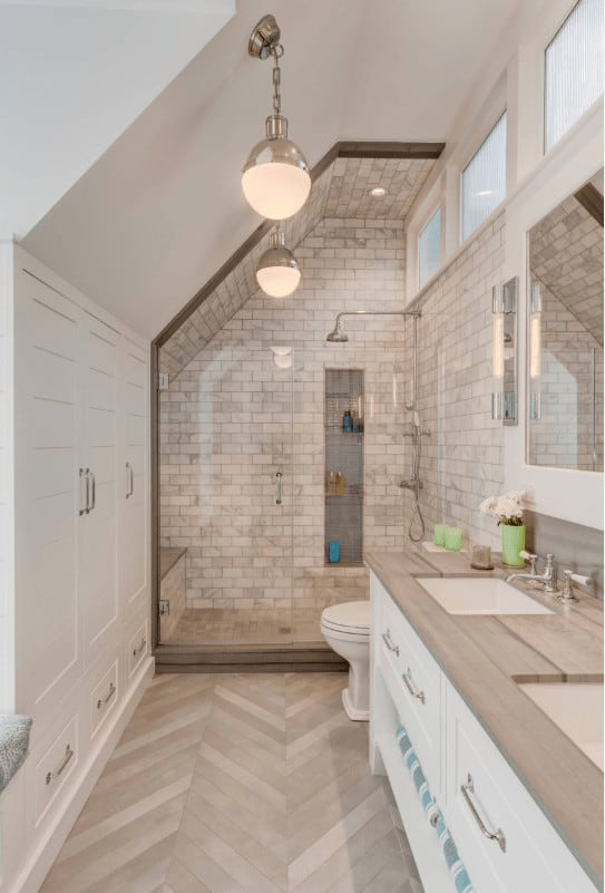 White bathroom with inset storage and walk-in shower clad in brick marble tiles. It has chevron wood flooring and vaulted ceiling with hanging glass globe pendants.