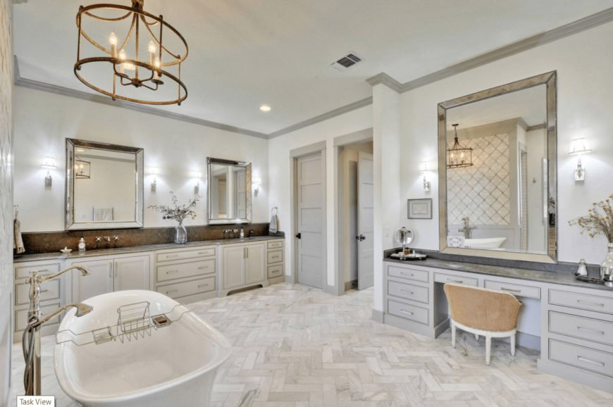 Elegant bathroom showcases dual washstand and a gray vanity paired with a round back chair. It includes a pedestal bathtub on a herringbone flooring lighted by a brass chandelier.
